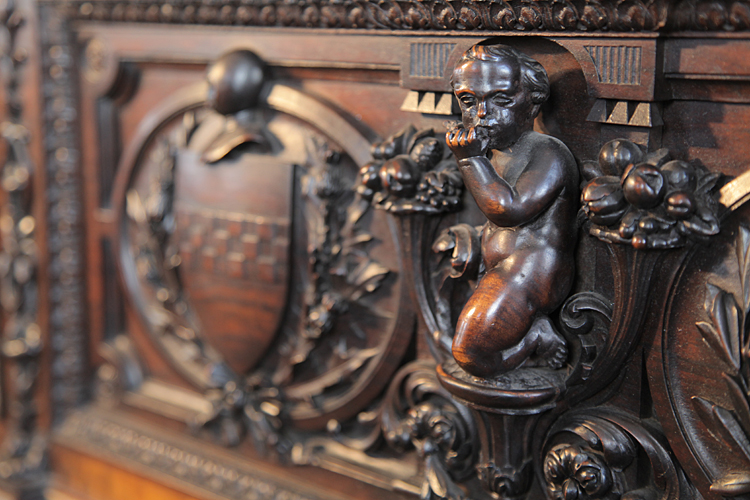 Detail of a carved cherub playing a musical instrument between two crests