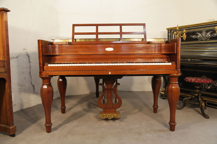 Front view of this Steinway model M piano showing the five baluster legs, high piano cheeks,  open work music desk and traditionally shaped piano lyre
