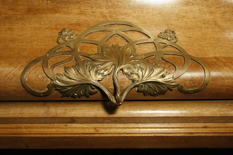 This ornate, brass handle in a scrolling foliage design, sits on the piano fall