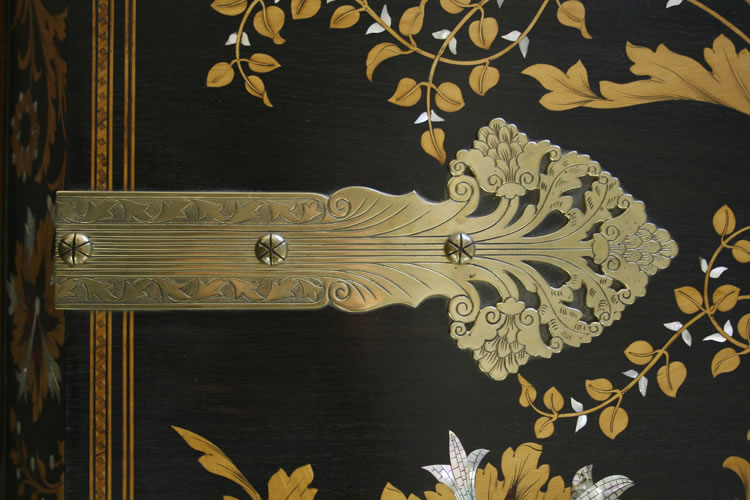 The stamped hinges continue the themes of foliage and flowers found in the cabinet inlay