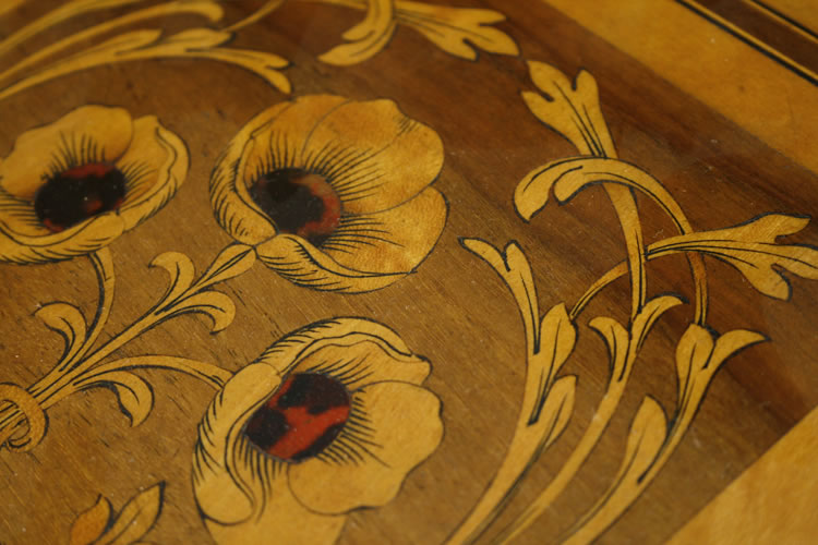 Poppies appear on the piano's music desk. They are inlaid with etched wood with a tortoiseshell centre