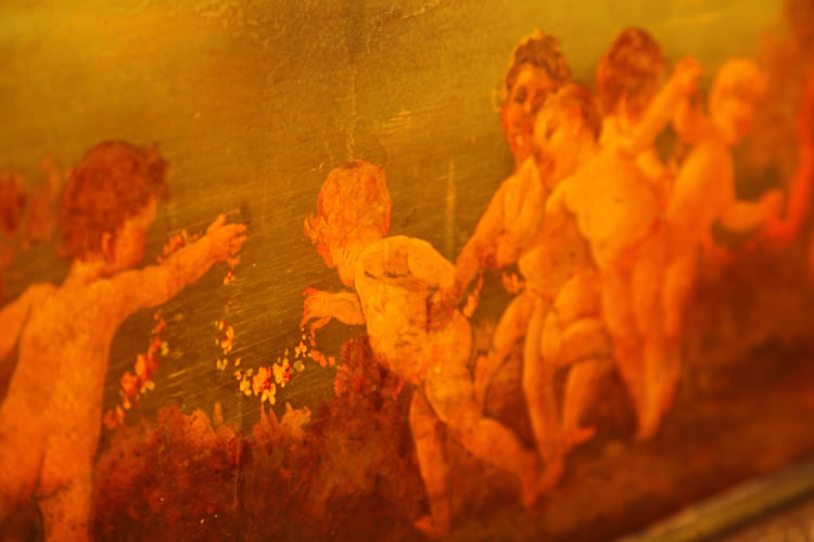 Hand-painted detail of dancing cherubs